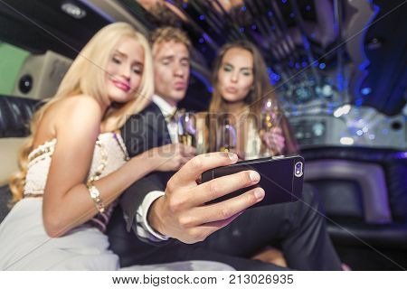 Young man is taking a selfie with two beautiful woman in a limousine to share with his friends
