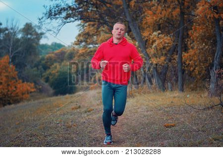 A Slim Strong Man Runs On The  Colorfull Autumnall Forest Hill.