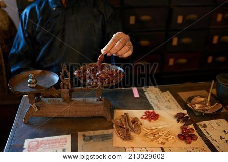 Traditional Asian apothecary worker weighting dried berries