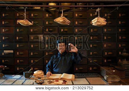 Happy traditional Asian apothecary worker showing bottle with medicine