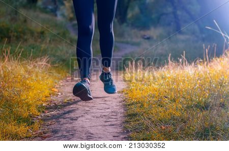 Close-up of an athlete's legs in black leggins and black sneakers. Jogger woman running along the path on the autumnall forest.