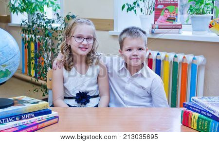 Two Small Schoolchildren, Pretty Little Girl And Boy, Sitting Together At Table In Class, Looking At