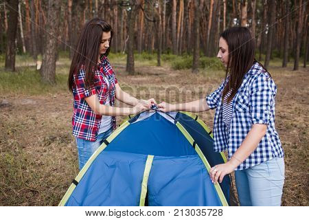 Friends set up tent together for camp rest. Tourist lifestyle. Bail out a friend, help support teamwork concept
