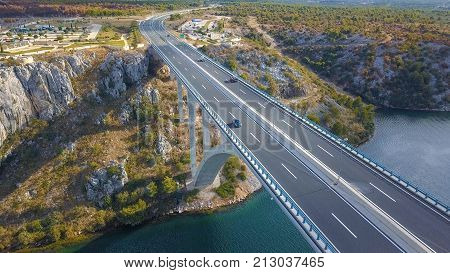 Aerial panorama view with bridge and sea around islands. Beautiful landscape surrounded with blue sea with bridge between. Autostrada bridge with traffic over Krka river at sunny day in Croatia.