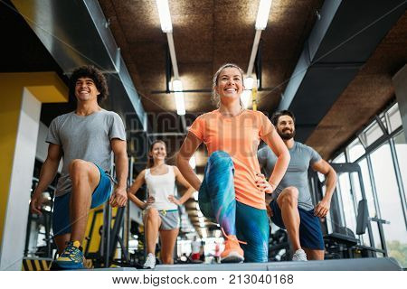 Group of young people doing exercises together in gym