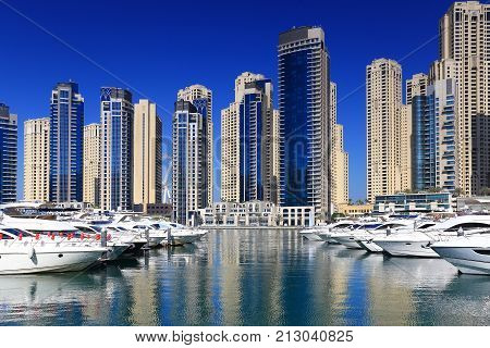 Luxury residential block with marina. White yachts in marina bay on skyscrapers background. Luxury marina bay district in Dubai on a sunny day. Real estate theme.