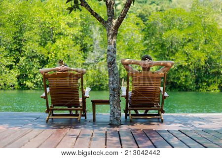 Summer landscape on tropical koh Kood island in Thailand. Panorama with young caucasian couple relaxing on sunbeds on Klong Chao.