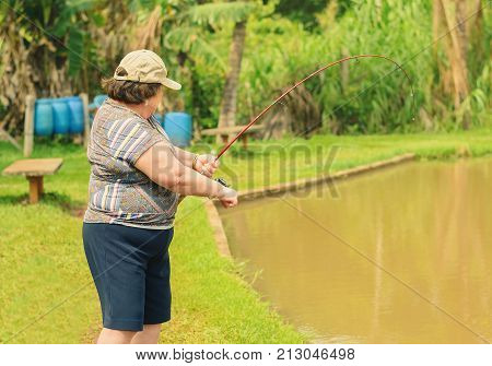 Old Woman Holding A Fishing Rod, Hooking A Fish On A Lake.