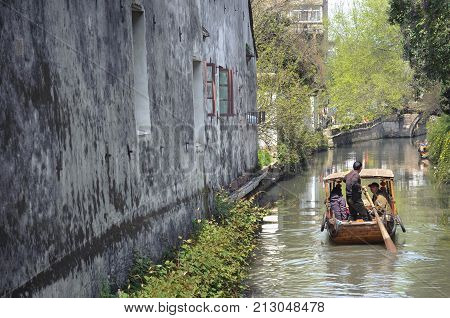 SUZHOU, CHINA - MARCH 31, 2013 - Traditional rowing boat taking tourists along the canal on Pingjianglu, Suzhou, China