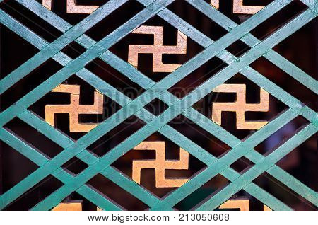 Buddhist manji symbol seen in a detail of a wooden window frame at a Hong Kong temple