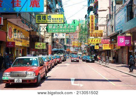JORDAN, HONG KONG - MARCH 23, 2014 - Taxis and shop signs in the Jordan area of Kowloon, Hong Kong.