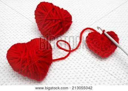 Red heart made of wool yarn and crochet heart. Soft focus. Handmade crocheted wool organic red heart. Old metal crocheting hook and two red yarn ball like a heart on the white crochet background