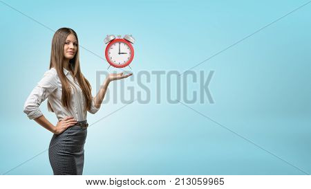 A blond businesswoman stands and holds one hand palm up with red retro alarm clock hovering above it. Business assistant. Schedule and timetable. Time management.