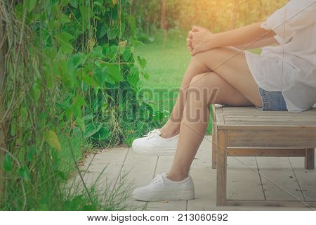 Relaxation Concept : Woman wear white shirt and short jean, her relaxing on wooden chair at outdoor garden surrounded with green natural sunlight in the background.