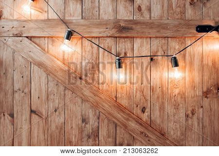 Christmas decoration on old grunge wooden board. warm gold garland lights on wooden rustic background.
