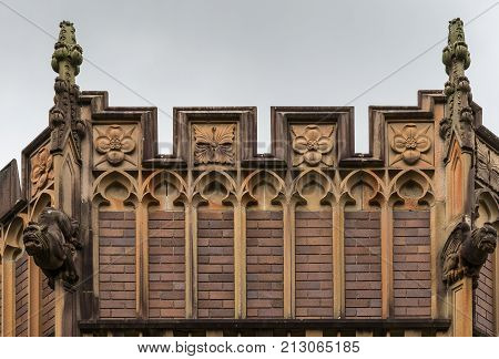 Sydney Australia - March 25 2017: Historic brown brick Wesley College of University of Sydney. Detail of facade with symbols gargoyles and towers.
