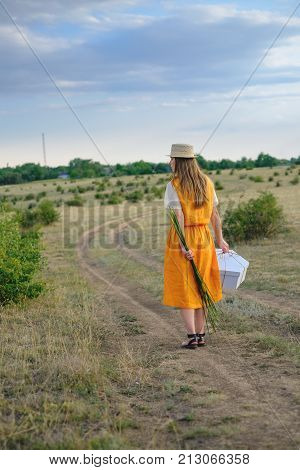 A girl in a straw hat and a gift box walks