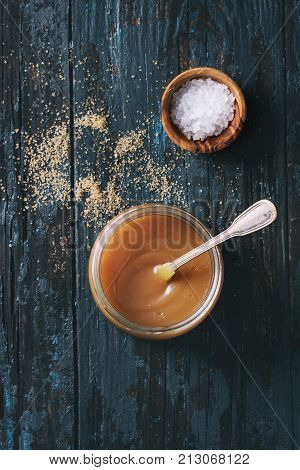 Glass jar of homemade salted caramel sauce with spoon, brown sugar and bowl of salt. Over old dark blue wooden background. Top view with space. Toned image