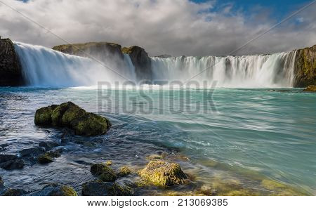Summer picture of one of the most spectacular waterfalls in Iceland - Godafoss. Cloudy day with sun