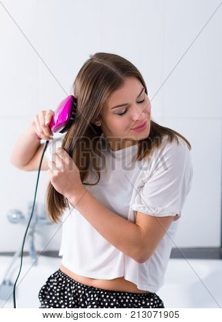 Woman With A Hot Straightening Brush