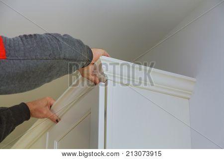 Carpenter Brad Using Nail Gun To Crown Moulding On Kitchen Cabinets