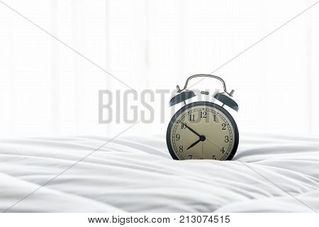 Vintage Alarm clock get up on white bed sheet duvet and pillow in morning with sunnny day. Lifestyle Concept