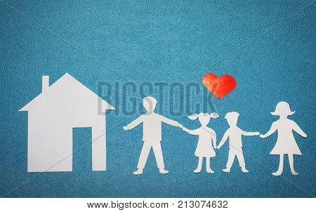 Family and home love concept. Paper house and family on blue textured background. Red heart over family and home silhouettes