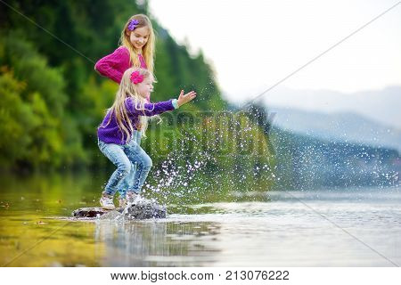Adorable Sisters Playing By Hallstatter See Lake In Austria On Warm Summer Day. Cute Children Having