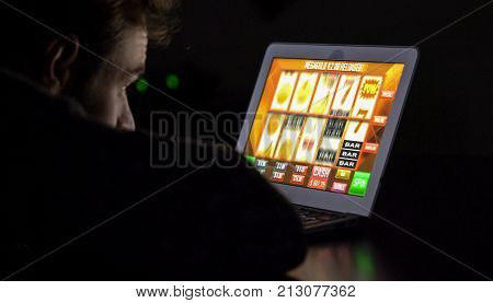 Gambling addicted man in front of online casino slot machine on laptop computer at night - loosing his money. Dramatic low light grain shot.