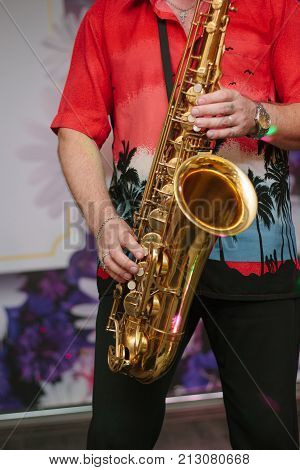 Saxophone player with the saxophone in arms, playing with it