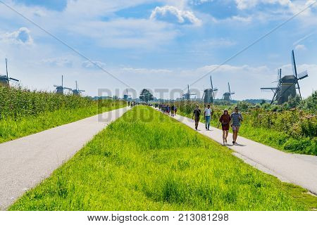 ROTTERDAM HOLLAND -AUGUST 22 2017; Tourists walk along path between two rows windmills in Kinderdijk district popular tourist destination with it's scenic fields ponds canls and windmills.