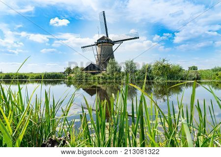 Windmill across water in Kinderdijk district popular tourist destination with it's scenic fields ponds canls and windmills near Rotterdam Holland.