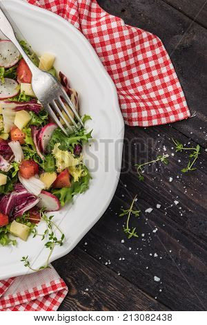 Fresh salad with mixed greens radish cheese and tomato in a plate on wooden background. Italian Mediterranean or Greek cuisine. Vegetarian vegan food. Fresh salad with mixed greens radish cheese and tomato in a plate on wooden background. Italian Mediterr