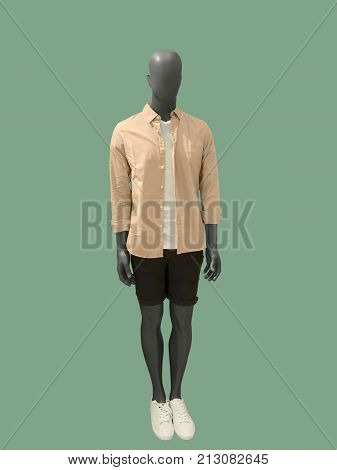 Full-length male mannequin dressed in casual summer clothes isolated on green background. No brand names or copyright objects.