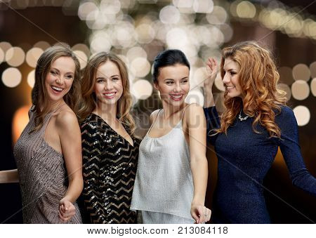 party, holidays, christmas and people concept - happy young women dancing over night lights background