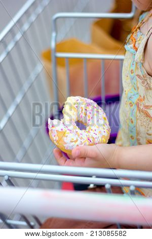 Hand with bitten donut. Girl holding donut at arm.