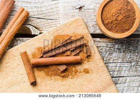 Cinnamon sticks and milled cinnamon spice on old table.