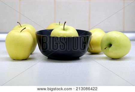 Still life with many ripe yellow apples in the kitchen on the table and bowl front view closeup