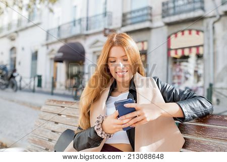 Cheerful stylish city girl using smart phone and sitting on bench. Happy business lady working outdoors. Positive student girl interacting on social media. Technology concept