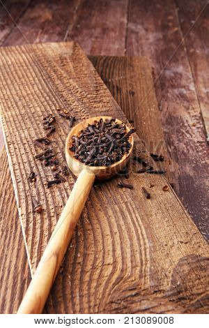 Many Dry cloves spice on brown wooden spoon.