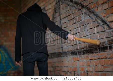 A street hooligan in a black hood at a construction site struck a brick red brick wall with a wooden bat.