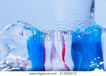 View of colorful tooth brush under water fall.