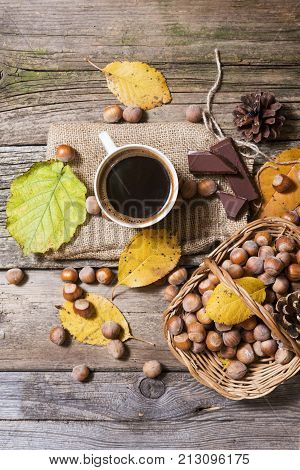 top view of black coffee on wooden table with hazelnuts basket with fallen leaves, chocolate and pinecone decoration. coffee drink with food decoration from above perspective