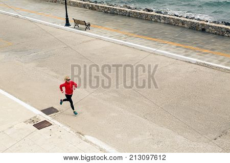 Woman Running On City Street At Seaside