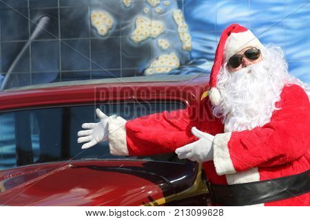 Santa Claus Smiles and Waves from his Hot Rod Car.