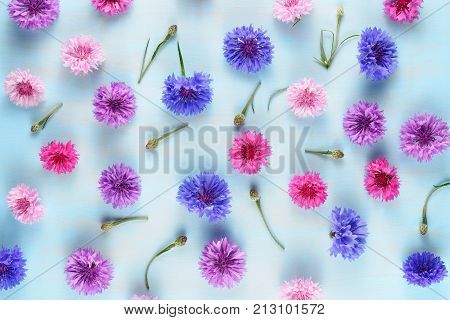 Floral background with cornflowers on blue table