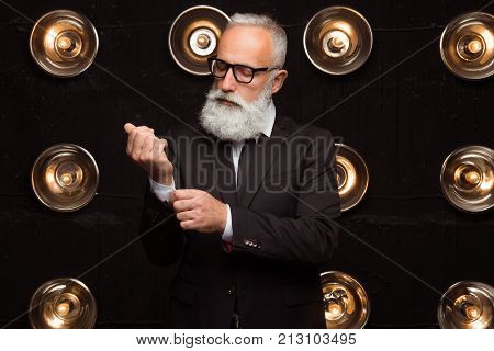 Fashionable bearded man in suit straightens the sleeve on the shirt. Fashion man in glasses makes a neat appearance. Neat and well-groomed man
