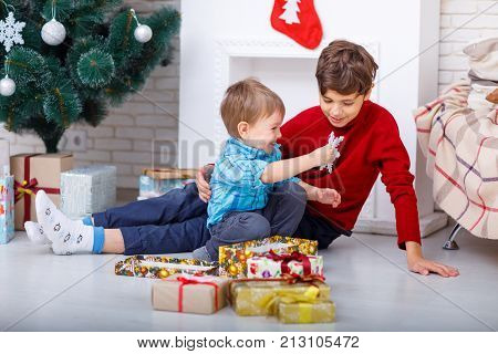 Portrait of charming brothers who sit on the floor next to New Year's gifts, the younger brother is playing with a snowflake.