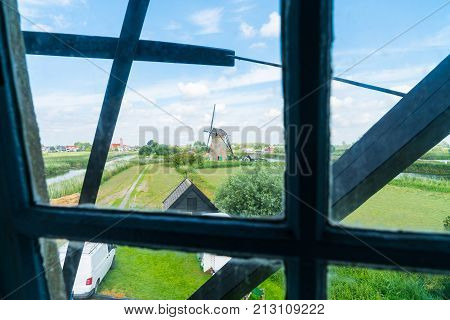 View through window frame of traditional windmill to landscape outside in Kinderdijk district popular tourist destination with it's scenic dykes fields ponds canals and windmills.
