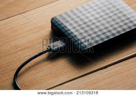Portable External Hard Disk Drive With Usb Cable On Wooden Background.